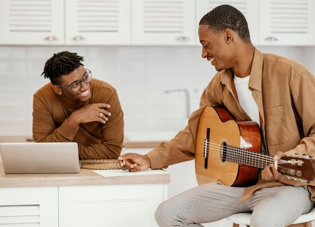 Männlicher smiley-musiker zu hause auf stuhl, der gitarre spielt und laptop verwendet Kostenlose Fotos