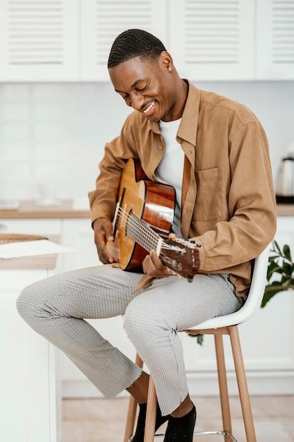 Männlicher smiley-musiker zu hause auf stuhl, der gitarre spielt Kostenlose Fotos
