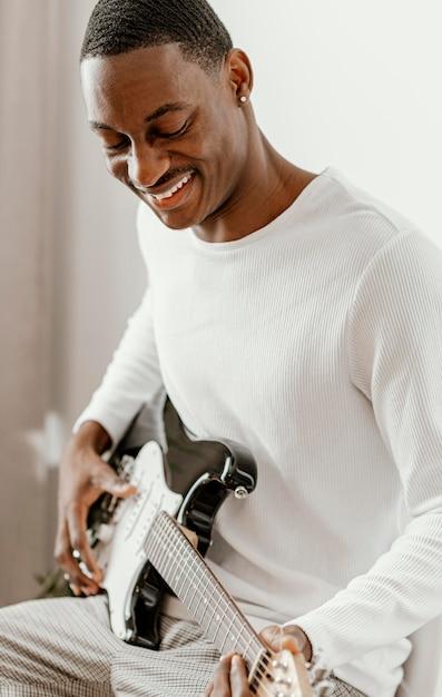 Männlicher smiley-musiker zu hause, der e-gitarre spielt Premium Fotos