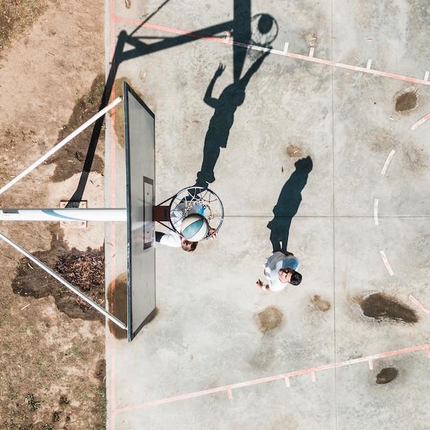 Männlicher spieler zwei, der mit ball am gericht draußen übt Kostenlose Fotos