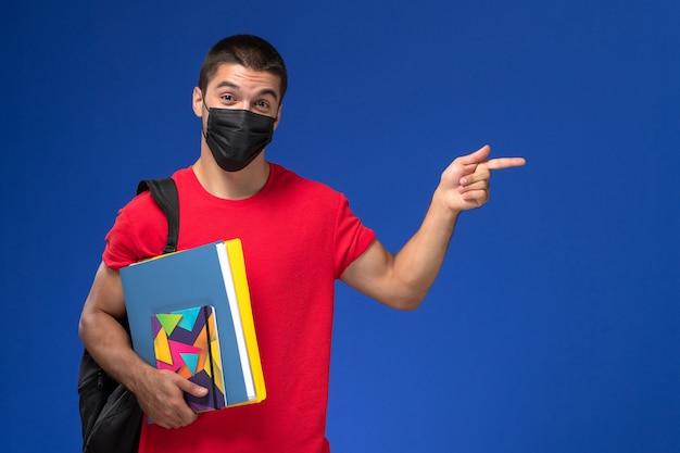 Männlicher student der vorderansicht im roten t-shirt, das rucksack in der schwarzen sterilen maske hält, die dateien auf dem blauen hintergrund hält. Kostenlose Fotos