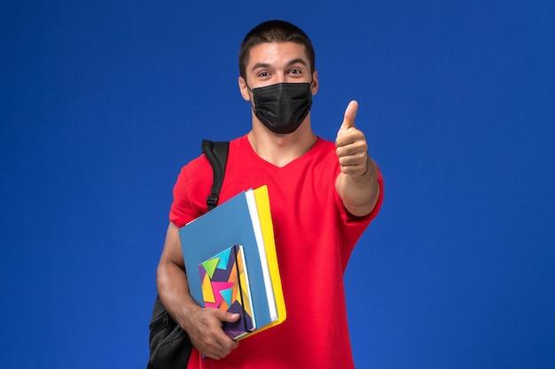 Männlicher student der vorderansicht im roten t-shirt, das rucksack in schwarzer steriler maske trägt, die hefte auf dem blauen hintergrund hält. Kostenlose Fotos