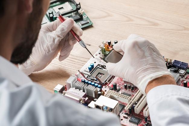 Männlicher techniker, der an computermotherboard arbeitet Kostenlose Fotos