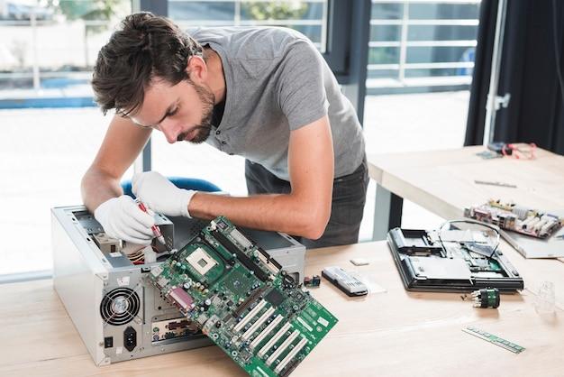 Männlicher techniker, der computer in der werkstatt repariert Kostenlose Fotos