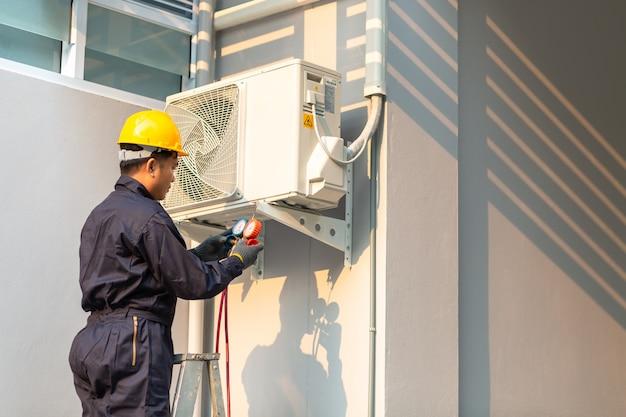 Männlicher techniker, der klimaanlagensicherheitsuniform repariert Premium Fotos