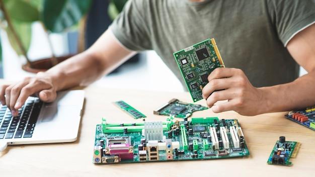 Männlicher techniker, der motherboard unter verwendung des laptops repariert Kostenlose Fotos