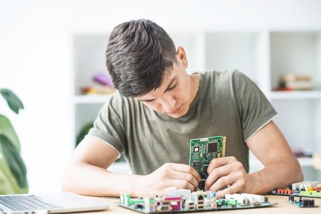 Männlicher technikstudent, der das hardware-teil zusammenbaut Kostenlose Fotos