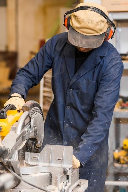 Männlicher tischler, der einige elektrowerkzeuge für seine arbeit in einem woodshop verwendet Kostenlose Fotos