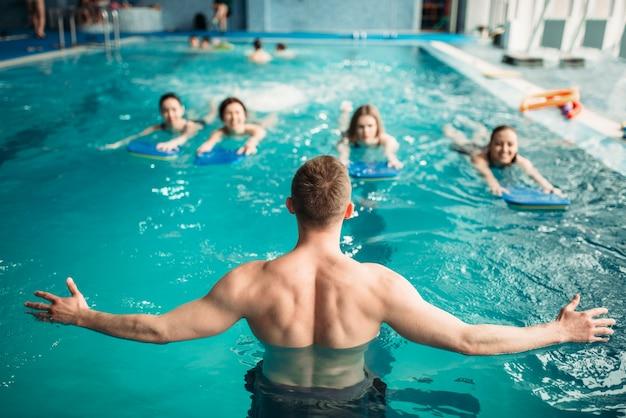 Männlicher trainer arbeitet mit weiblicher gruppe beim training im schwimmbad. aqua aerobic training, wassersport Premium Fotos