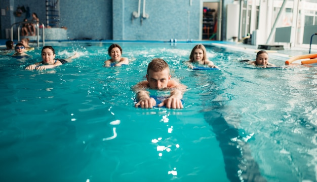 Männlicher trainer schwimmt mit weiblicher aqua-aerobic-gruppe Premium Fotos