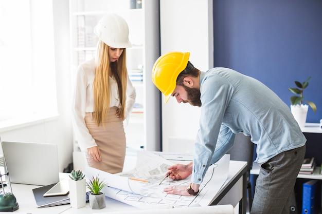 Männlicher und weiblicher ingenieur, der an plan im büro arbeitet Kostenlose Fotos