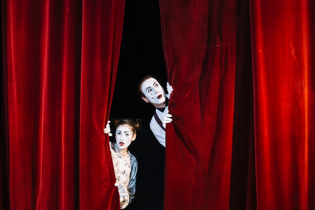Männlicher und weiblicher pantomimekünstler, der vom roten vorhang späht Kostenlose Fotos