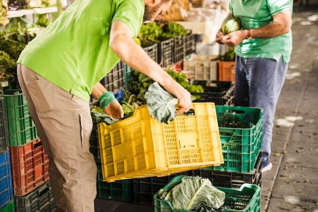 Männlicher verkäufer, der gemüsekiste am markt vereinbart Kostenlose Fotos