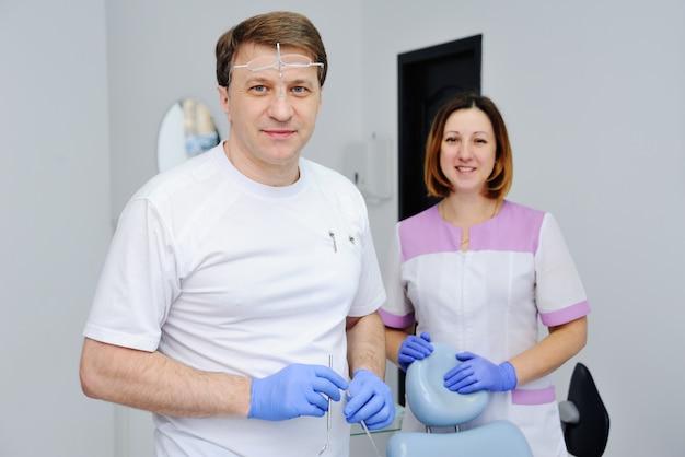 Männlicher zahnarzt mit behilflichen medizinischen instrumenten und mädchen in der klinik Premium Fotos