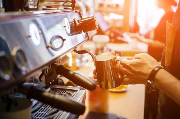 Männliches barista machen kaffee lattekunst im kaffeestubecafé Premium Fotos