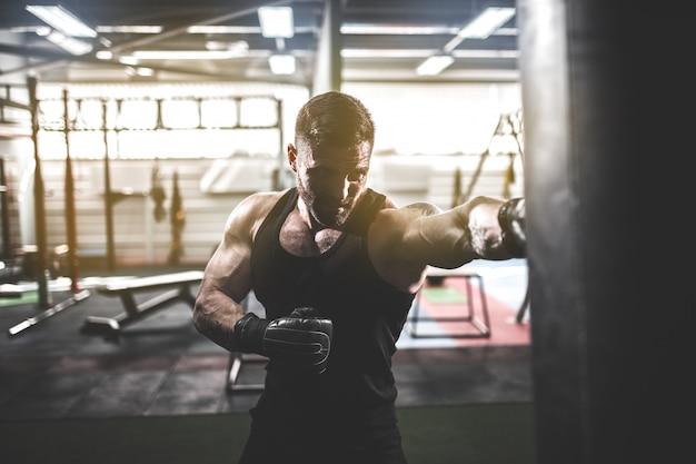 Männliches boxertraining mit sandsack in der dunklen sporthalle. Premium Fotos
