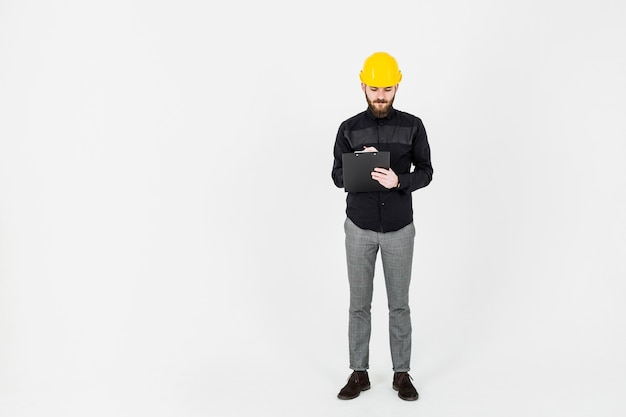 Männliches ingenieurschreiben auf klemmbrett über weißem hintergrund Kostenlose Fotos