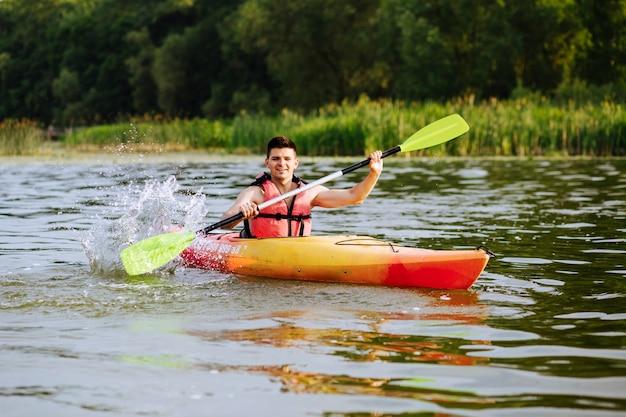 Männliches kayaker, das wasser beim kayak fahren auf see spritzt Kostenlose Fotos