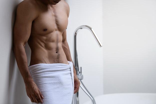 Männliches model mit weißen handtuch im badezimmer Premium Fotos
