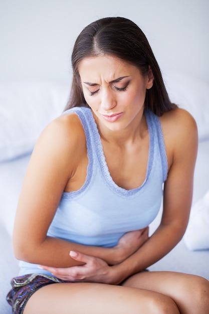 Magenschmerzen. ungesunde junge frau mit den magenschmerzen, die sich zu hause auf dem bett lehnen Premium Fotos
