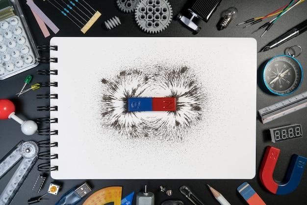 Magnetfeld der wissenschaftlichen ausrüstung, des zubehörs und des stangenmagneten auf weißem notizbuch. Premium Fotos