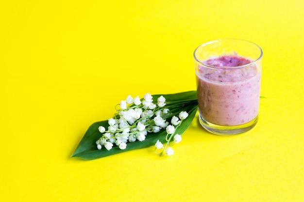 Maiglöckchen. frischer beere smoothie auf einem gelb. maiglöckchen und smoothies von beeren. frühling Premium Fotos