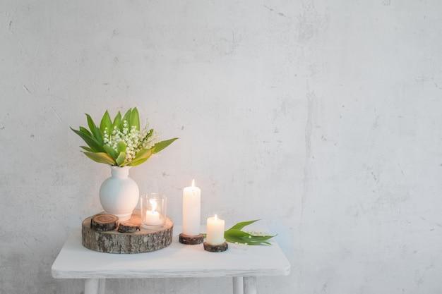 Maiglöckchen in vase mit kerzen auf oberfläche alte weiße wand Premium Fotos