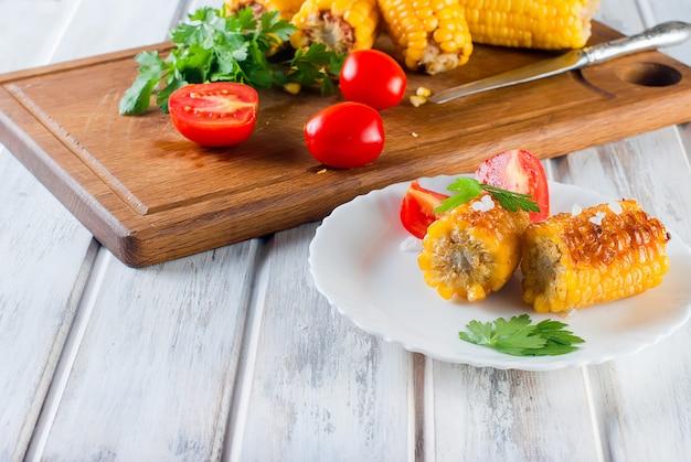 Mais gegrillt mit tomaten und grüns auf einer platte Premium Fotos