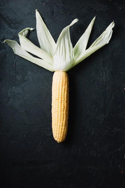 Mais mit blättern auf einer draufsicht des schwarzen schmutzhintergrundes Kostenlose Fotos