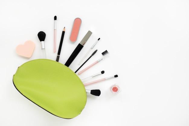 Make-up-kosmetik in einer hellgrünen kosmetikerin auf weiß Premium Fotos