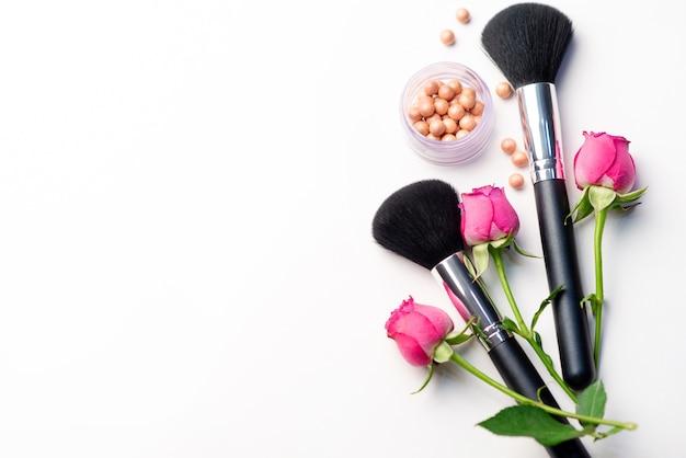 Make-up pinsel, blumen und erröten auf einem weißen hintergrund. beauty-konzept. nahaufnahme mit platz für text Premium Fotos