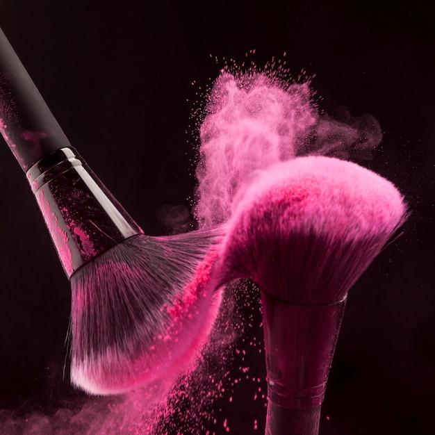 Make-up pinsel mit rosa puderdunst Kostenlose Fotos