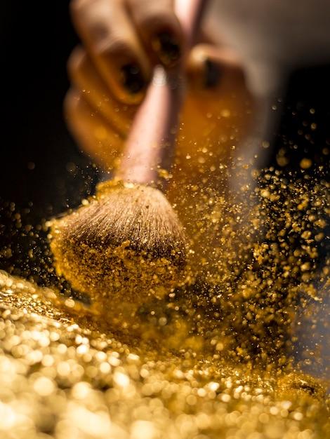 Make-upbürste mit dem goldenen kosmetischen pulver, das auf schwarzen hintergrund verbreitet Premium Fotos