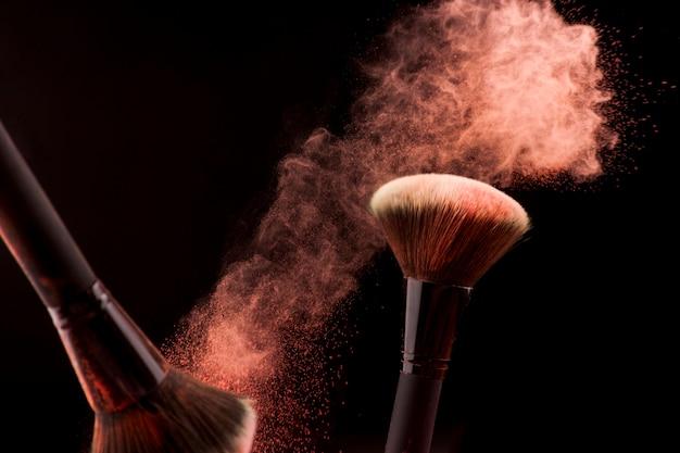 Make-upbürsten im staub des roten pulvers auf dunklem hintergrund Kostenlose Fotos
