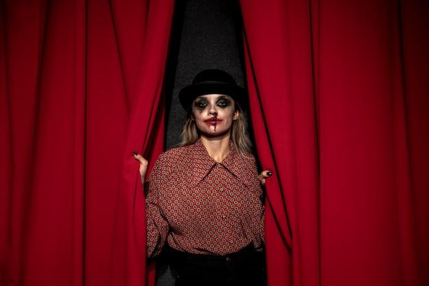 Make-upfrau, die einen roten theatervorhang hält Kostenlose Fotos