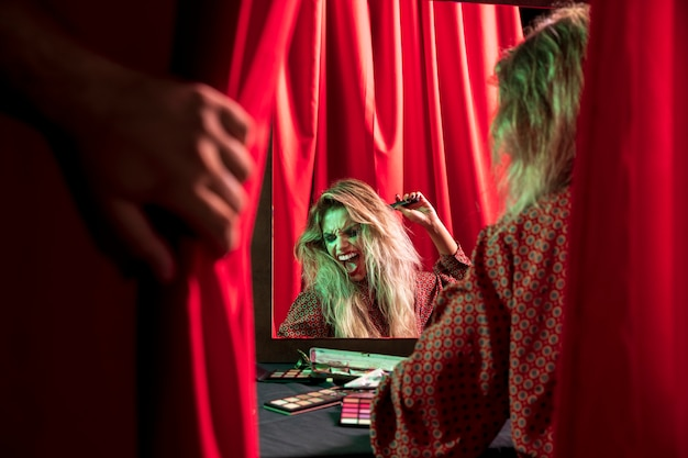 Make-upfrau für halloween, das vor einem spiegel spielt Kostenlose Fotos