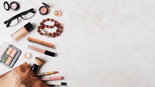 Make-upkosmetik mit zubehör auf heller oberfläche Premium Fotos