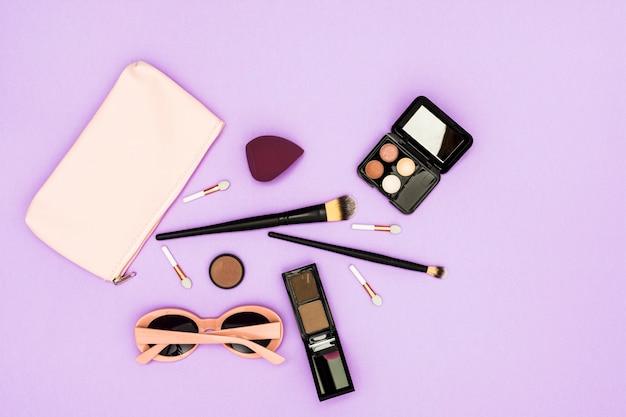 Makeup bürsten; lidschatten-palette und sonnenbrillen auf lila hintergrund Kostenlose Fotos