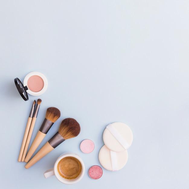 Makeup bürsten; lidschatten; rouge und schwamm mit kaffeetasse auf blauem hintergrund Kostenlose Fotos