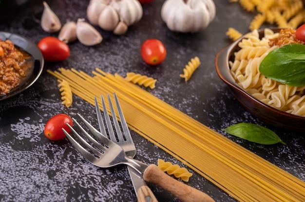 Makkaroni mit tomaten und basilikum auf einem grauen teller anbraten. Kostenlose Fotos
