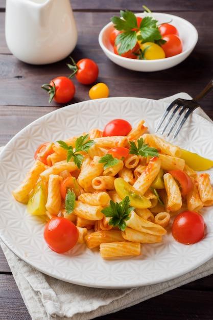 Makkaroni, teigwaren in tomatensauce und käse in einer platte auf einem holztisch Premium Fotos