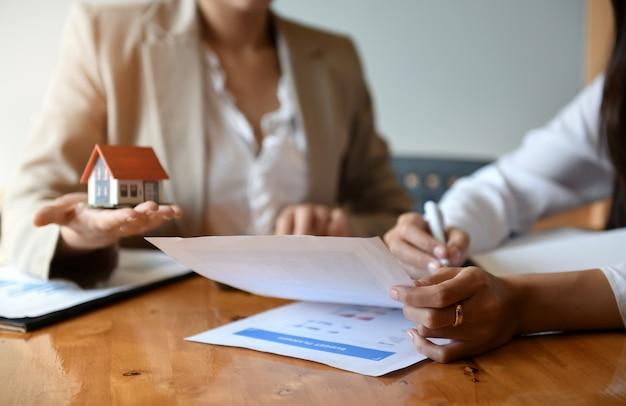 Maklerhausverkäufe arbeiten an der tabelle. sie hält stift- und hausmodell in der hand. Premium Fotos