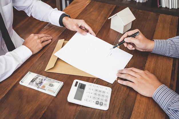 Maklervertreter präsentiert und konsultiert den kunden detailliert, um die entscheidung über ein wohnungsbaudarlehen zu treffen, um eine formularvereinbarung zu unterzeichnen Premium Fotos