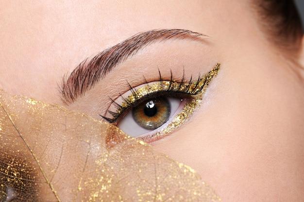 Makroaufnahme des weiblichen auges der schönheit mit goldenem eyeliner-make-up bedeckt künstliches gelbes blatt Kostenlose Fotos