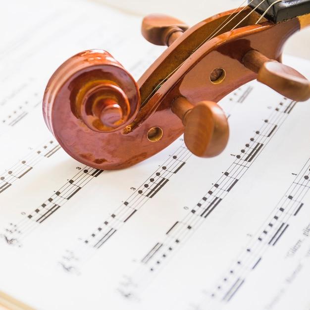 Makroschuß der hölzernen violinenrolle und -schnüre auf musikalischen anmerkungen Kostenlose Fotos