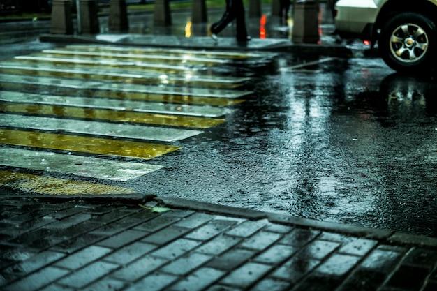Makroschuß des nassen stadtstraßen-bodenkopfsteins während des regens in europa Premium Fotos