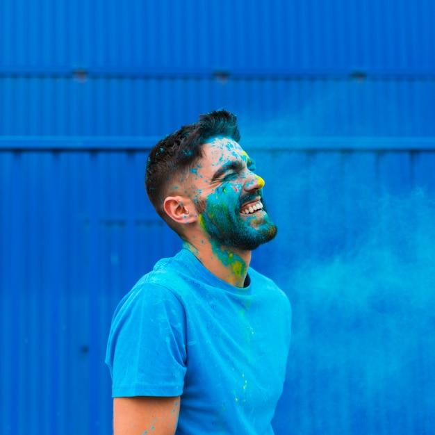 Malen sie den befleckten jungen mann, der auf holi-festival lacht Kostenlose Fotos