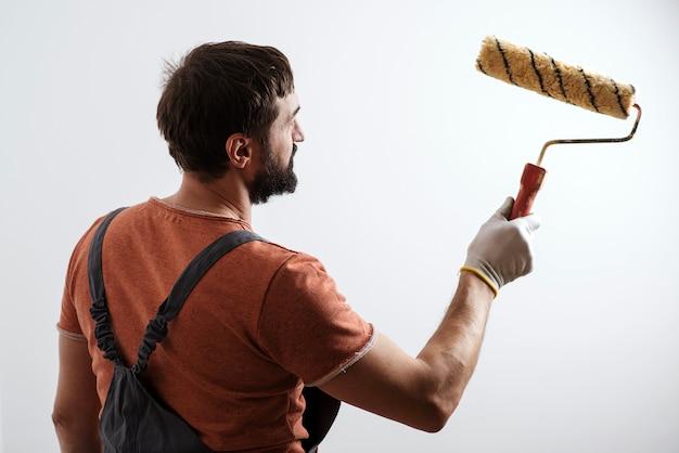 Maler arbeitet. hausrenovierungskonzept. geschickter und professioneller maler. pinselwalzenmaler. Premium Fotos