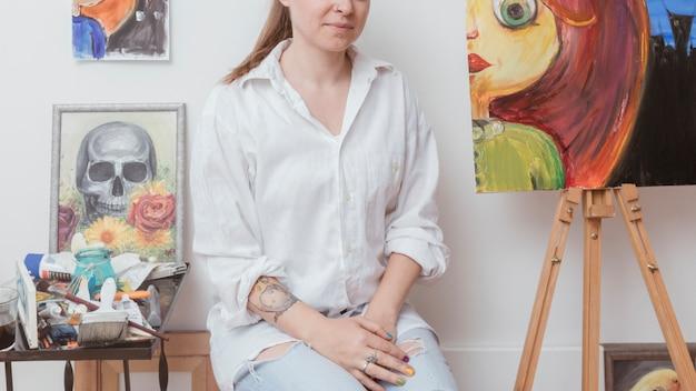 Maler, der im kreativen studio sitzt Kostenlose Fotos