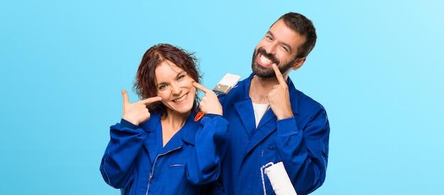 Maler, die mit einem angenehmen ausdruck lächeln, während sie den mund mit den fingern zeigen Premium Fotos